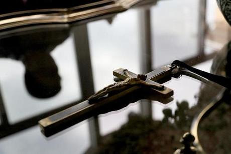 (FOR FUTURE PUBLICATION.)Seneca, South Carolina, 08/09/17, Jim Graham, son of a Catholic priest, in his home, reflected in coffee table with his father's crucifix on table. Suzanne Kreiter/Globe staff