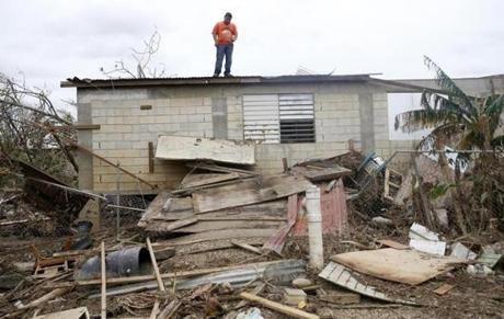 "Toa Baja, Puerto Rico -- 9/30/2017 - Miguel Martinez, 28, stands on what is left of the roof of his home as he waits for crews with heavy machinery to come and clear away the debris from Hurricane Maria. Martinez has been working for two years to construct the home which used to belong to his grandmother and then he said, ""in 24 hours, all gone."" Martinez knew the home was prone to flooding but it was all he and his wife could afford. (Jessica Rinaldi/Globe Staff) Topic: Reporter:"