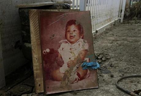 Toa Baja, Puerto Rico -- 9/30/2017 - A baby picture is covered in mud outside of a home in Toa Baja after Hurricane Maria. (Jessica Rinaldi/Globe Staff) Topic: Reporter: