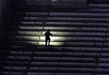 Oct, 18, 2017-Allston, Ma- 6:10 AM- A cellphone flashlight helps a stairclimber navifate the steps of Harvard Stadium. All are welcome and admission is free for the stair-climbing every Wednesday morning as part of the November Project at Harvard Stadium