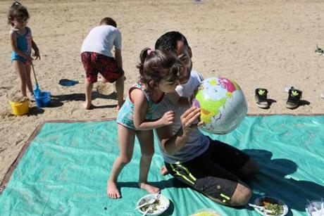 NOT FOR GETTY. Concord, Ma., 07\16\17, Abdulkader holds up an inflatable beach ball, a map of the world on its surface, and told his daughter Fatima to kiss the tiny spot that was Syria. (Suzanne Kreiter/Globe staff