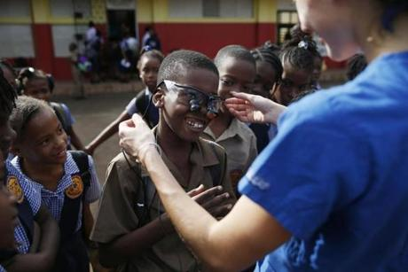 A boy at Brown's Town Primary School laughed as Tufts Dental Student Toria Koutras fitted him with the glasses that she uses to examine teeth.