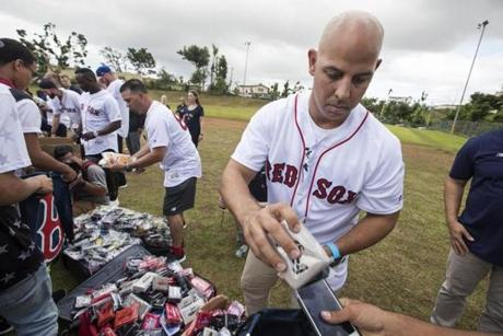 Alex Cora and other team representatives distributed baseball supplies.