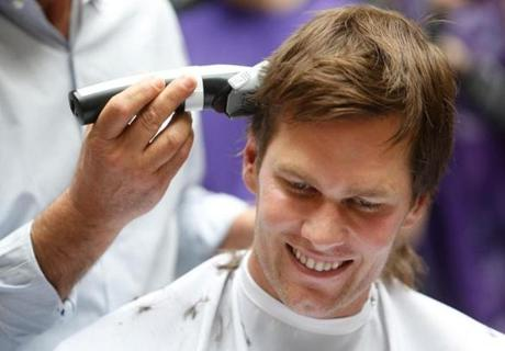 Quincy, MA -- 3/08/2018 - New England Patriots quarterback Tom Brady smiles as he gets his head shaved as part of Saving By Shaving 5. (Jessica Rinaldi/Globe Staff) Topic: HaircutBenefit Reporter: