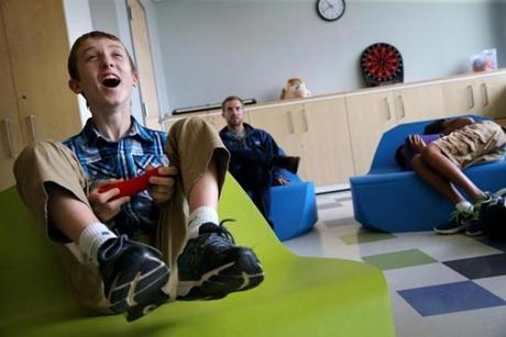 Southborough, MA- August 16, 2017: Connor Biscan, 13, played a Super Mario Brothers video game in the leisure center at the New England Center for Children in Southborough last August. At the residential school for children with autism, even play time is an opportunity for adults to teach students social skills. Teachers talk through game strategy and cheer successful moves to encourage the boys to follow directions and to promote good sportsmanship. (Craig F. Walker/Globe Staff) section: metro reporter: kowalczyk
