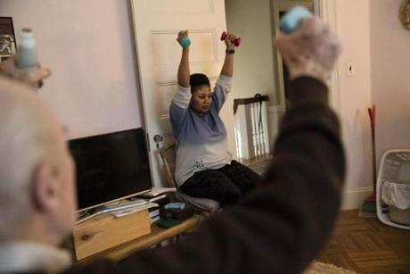 Newton, MA - 2/4/2018 Rita Sarpong tends to her 90-year-old patient at his home in Newton, MA, Feb. 4, 2018. She is guiding him through his daily exercises. Sarpong, a Ghanaian immigrant, works two jobs as a home health care aide. (Keith Bedford/Globe Staff) homeaides