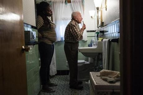 Newton, MA - 2/13/2018 - Caregiver Aba Owusu watches as her client Ned DeRubeis(91) shaves at his home in Newton, MA, Feb. 13, 2018. Owusu, a visa lottery winner from Ghana, spent four overnight shifts a week tending to the elderly DeRubeis's needs. (Keith Bedford/Globe Staff) homeaides NOTE: DeRubeis died three months later (May 23)