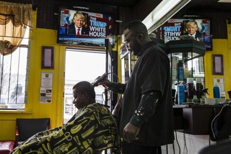 Worcester, Massachusetts - 3/1/2018 - A Ghanaian barber cuts a customer's hair while an image of President Trump appears on the screen on Main Street in Worcester, Massachusetts, March 1, 2018. Worcester is home to one of the largest Ghanaian communities in the United States. Many Ghanaian home care workers live in the Worcester area, where there's an abundanceof shops and restaurants catering to people from Ghana, more than Ghanaian churches, and multiple money transfer kiosks so they can efficiently send money back home.(Keith Bedford/Globe Staff) homeaides