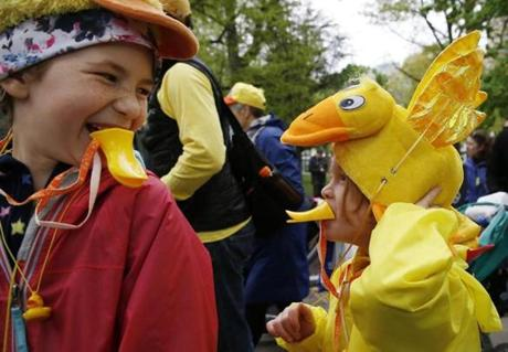 Boston, MA--5/13/2018-- Siri Carr, 10, of Beverly laughs as her brother David, 7, flaps the duck wings on his hat as the two take part in the Duckling Day parade. (Jessica Rinaldi/Globe Staff) Topic: 14duckling Reporter:
