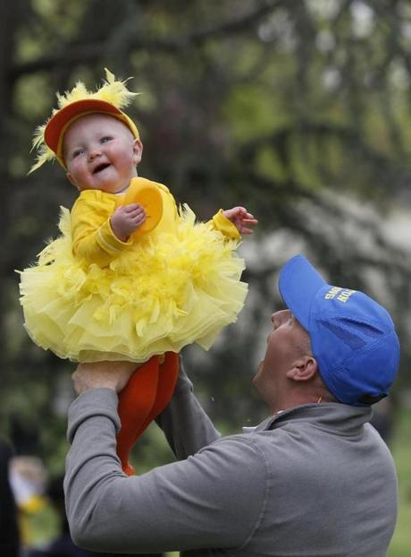 Murdock Smith of Beverly lifted up his 10-month-old daughter, Olivia, after the parade.