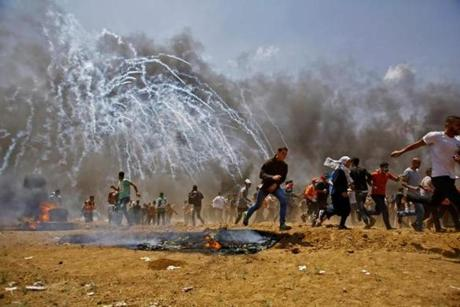 Palestinians ran for cover from tear gas fired by Israeli security forces along the Gaza border on Monday.
