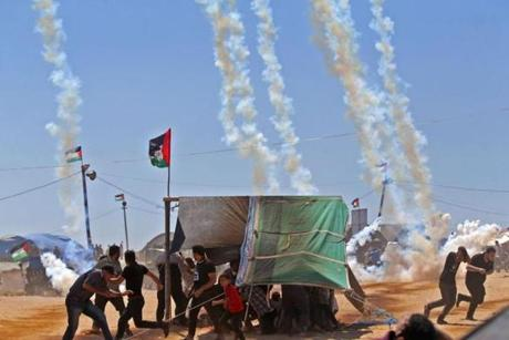 Palestinians ran for cover from tear gas near the border between Israel and the Gaza Strip, east of Jabalia, on Monday, as they protested the opening of the US embassy following its controversial move to Jerusalem.