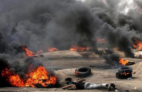 A Palestinian pushed a burning tire during the protests on the Gaza-Israel border on Monday.