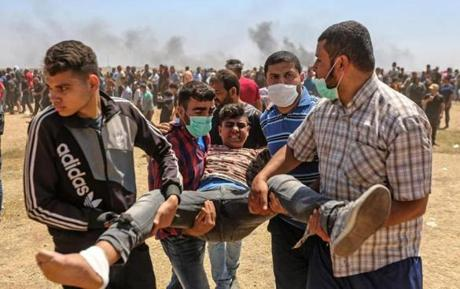 Palestinians carried an injured protester during the protests on Monday near the border between the Gaza strip and Israel east of Gaza City.