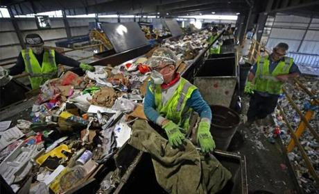 Workers attempted to dig trash from recyclables at E.L. Harvey & Sons. Many nations have cracked down on receiving tainted recyclables.