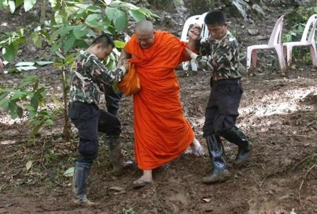 A Buddhist monk, helped by Thai rescuers, walked after praying near the cave complex.