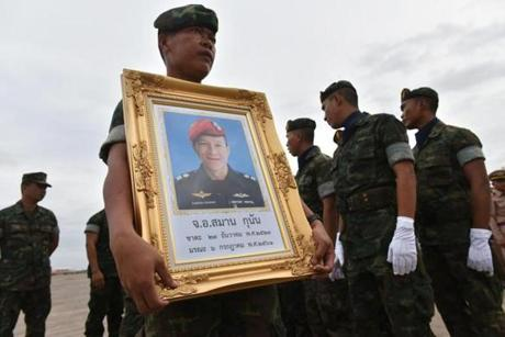 "A Royal Thai Navy soldier carries a portrait of Saman Gunan, a former navy SEAL who died in an accident in Tham Luang cave in a rescue mission for the trapped 12 boys and their coach during arrival honors for Gunan's remains at a military base in Chon Buri province on July 6, 2018. A former Thai navy diver helping to rescue a football team trapped inside a flooded cave died July 6 as officials warned the window of opportunity to free the youngsters is ""limited"". / AFP PHOTO / THAI NEWS PIX / Panumas SANGUANWONGPANUMAS SANGUANWONG/AFP/Getty Images"
