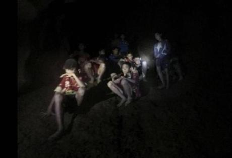 FILE - This Monday, July 2, 2018, file photo provided by Tham Luang Rescue Operation Center shows a group of Thai youth soccer players and their coach as they were found in a partially flooded cave in Mae Sai, Chiang Rai province, northern Thailand. For the boys and their coach, we have only a hint of what it might have been like. But for the rest of us, watching from afar as the world's journalists beamed us live shots and the unknowable became known drip by captivating drip, we knew only one thing: It was hard to look away. (Tham Luang Rescue Operation Center via AP, File)