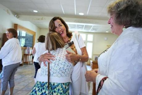 Hanson, MA - 9/2/18 - Lector Marilyn Shaw (cq) (facing center) embraces Rachel Tamulevich (cq) after Mass. Rebecca Shipman Hurst (cq), right, asked people to wear white. Father Michael Hobson (cq) celebrates Mass in St. Joseph the Worker Parish, as local Catholics deal with the current upheaval over cover-ups of sex crimes in the church. Photo by Pat Greenhouse/Globe Staff Topic: 09catholics Reporter: Jenna Russell