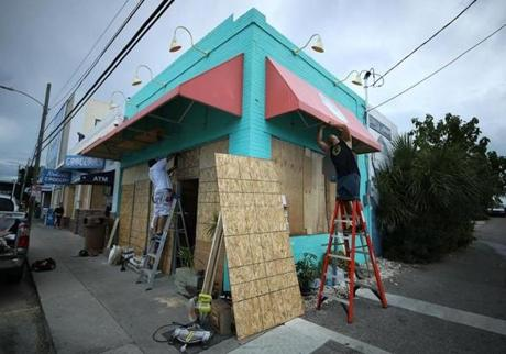 WRIGHTVILLE BEACH, NC - SEPTEMBER 11: Workers board up the Wrightsville Beach Art Co. while preparing for the arrival of Hurricane Florence on September 11, 2018 in Wrightsville Beach, United States. Hurricane Florence is expected on Friday possibly as a category 4 storm along the Virginia, North Carolina and South Carolina coastline. (Photo by Mark Wilson/Getty Images)
