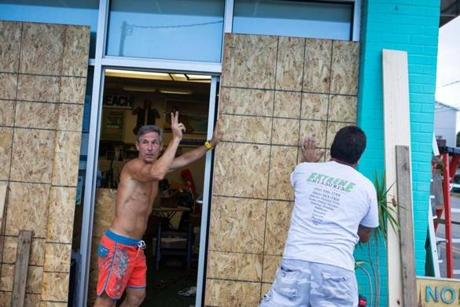 Jazz Undy, owner of Wrightsville Beach Art Co, waves to a friend as he helps board up his shop in anticipation of Hurricane Florence, on Wrightsville Beach, North Carolina on September 11, 2018. - More than a million people were under evacuation orders in the eastern United States Tuesday, where powerful Hurricane Florence threatened catastrophic damage to a region popular with vacationers and home to crucial government institutions. (Photo by Logan CYRUS / AFP)LOGAN CYRUS/AFP/Getty Images