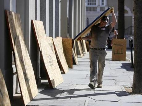 Preston Guiher carries a sheet of plywood as he prepares to board up a Wells Fargo bank in preparation for Hurricane Florence in downtown Charleston, S.C., Tuesday, Sept. 12, 2018. (AP Photo/Mic Smith)