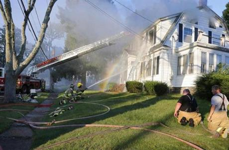 Firefighters battle a house fire, Thursday, Sept. 13, 2018, on Herrick Road in North Andover, Mass., one of multiple emergency crews responding to a series of gas explosions and fires triggered by a problem with a gas line that feeds homes in several communities north of Boston. (AP Photo/Mary Schwalm)