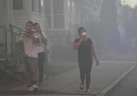 Lawrence, MA--9/13/2018-- People cover their faces to protect themselves from heavy smoke from a fire on Bowdoin Street in Lawrence. (Jessica Rinaldi/Globe Staff) Topic: Reporter: