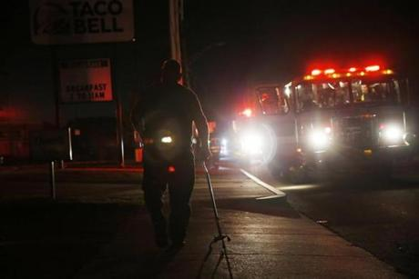 Lawrence, MA--9/13/2018-- A man is illuminated only by the light of fire trucks as he walks down the street in Lawrence. (Jessica Rinaldi/Globe Staff) Topic: Reporter:
