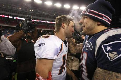 Foxborough, MA - 1/14/2012: Denver Broncos quarterback Tim Tebow (15, left) passes New England Patriots tight end Aaron Hernandez (81) after the game. Both went to the University of Florida. The New England Patriots play the Denver Broncos in the 2012 AFC Divisional Playoff Game at Gillette Stadium in Foxborough, MA on Jan. 14, 2012. (Matthew J. Lee/Globe Staff)
