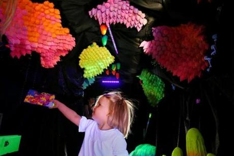 "Lucy Schwartz, 2, admired an art installation titled ""Neon Dream Crystal Cave"" while visiting the public art exhibition ""We The Future"" on display during HUBweek."