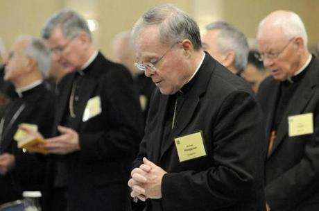 FILE - In this Nov. 10, 2008, Bishop Michael Hoeppner, center, of Crookston, Minn., prays during a semi-annual meeting of the United States Conference of Catholic Bishops in Baltimore. A lawsuit against Bishop Hoeppner has been filed accusing the bishop and diocese of concealing a report of abuse and threatening retaliation against a victim if he went public. (AP Photo/ Steve Ruark,File)