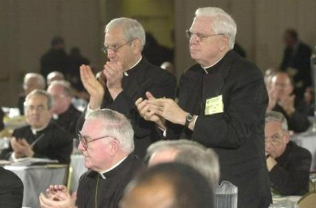 Cardinal Anthony Bevilacqua, Archbishop of Philadelphia, left and Cardinal Bernard Law of Boston lead the U.S. Conference of Catholic Bishops in a standing ovation after the Bishops' clerical sex abuse policy was approved in Dallas, Friday, June 14, 2002. After months of scandal that tore at the heart of the Roman Catholic Church, American bishops adopted a policy Friday that will bar sexually abusive clergy from face-to-face contact with parishioners but keep them in the priesthood. (AP Photo/Eric Gay) -- Library Tag 06152002 National-Foreign BOSTON GLOBE SPOTLIGHT SERIES: CHILD SEX ABUSE SCANDAL IN THE CATHOLIC CHURCH BISHOPS' CONFERENCE IN DALLAS, TEXAS catholicsexscandal