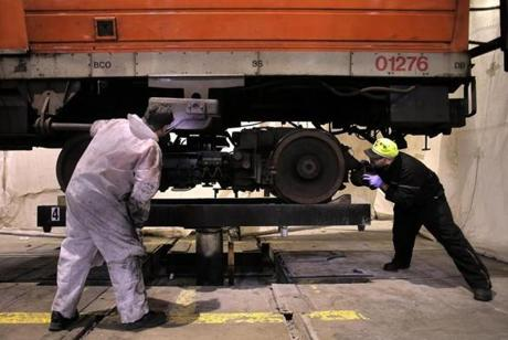 Repairers Phil Hardy and Gabriel Lopez moved a truck with a repaired motor into place beneath an Orange Line car to be reattached.