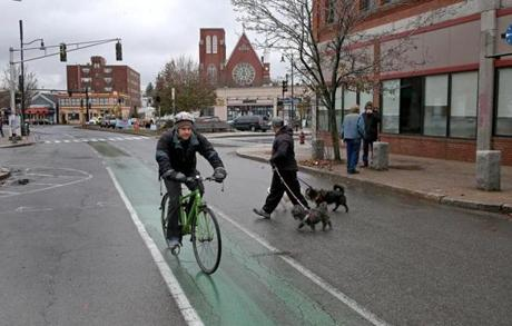 A dog walker crossed the street as a cyclists rode through Union Square in Somerville.