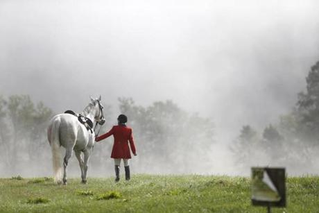 Shoreham, VT--9/23/2018-- Peggy Racine walks her horse, Stretch, over to the barn where the Blessing of the Hounds will take place before going out to lead the second field of riders in the club's first formal meet of the season during Green Mountain Hounds joint meet with Wentworth. (Jessica Rinaldi/Globe Staff) Topic: foxhunt Reporter: