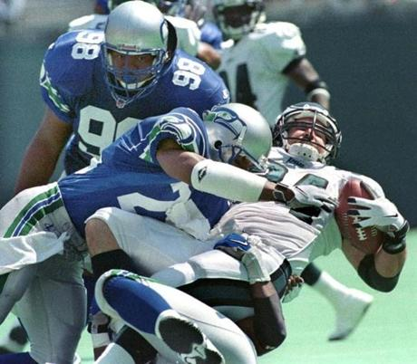 Kevin Turner (right) takes a hit during his days with the Eagles, in a game against the Seattle Seahawks.