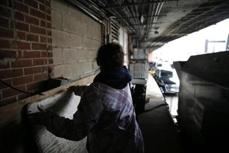 Boston, MA, 11/28/2018 -- Marie moves a piece of plywood behind the dumpster where she had given birth to a baby boy only a few days earlier. (Jessica Rinaldi/Globe Staff) Topic: 06christmasstory Reporter: Evan Allen