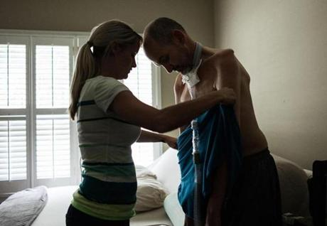 Allison Sanford, then his nurse and later his wife, helps Kevin Turner change his shirt in a December 2014 photo, with the effects of ALS apparent on the former fullback.