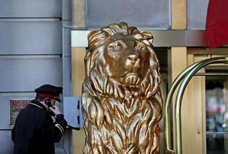 A doorman stood by one of the two gilded lions at the entrance to the Fairmont Copley Plaza Hotel. The lions, created by sculptor Alexander Pope, stood in front of the Hotel Kensington on Boylston Street until its demolition in 1967, later guarding the parking lot that replaced it until being purchased by the Copley Plaza in 1974.