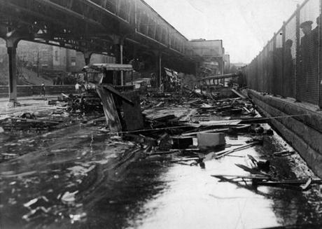 Boston, MA - 1/16/1919: Smashed vehicles and debris sit in a puddle of molasses on Commercial Street on Jan. 16, 1919, the day after a giant tank in the North End collapsed, sending a wave of an estimated 2.3 million gallons of molasses through the streets of Boston. Twenty-one people died and 150 were injured. (Boston Globe Archive/) --- BGPA Reference: 150115_MJ_004