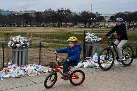 The White House is seen in the background as people bike past trash uncollected on the National Mall.