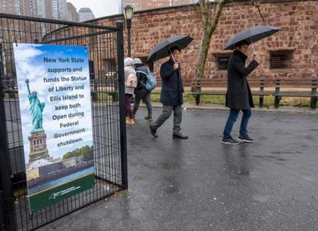 People walked past a sign announcing that New York funds are keeping the Statue of Liberty and Ellis Island open for visitors.