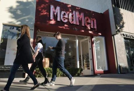 FILE - In this Thursday, Dec. 21, 2017, file photo pedestrians walk past one of the MedMen marijuana dispensaries in Los Angeles. Recreational marijuana sales became legal in California this year, and the industry is targeting tourists as well as locals, with tours, shops, lodging and ads. (AP Photo/Richard Vogel, File)