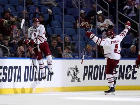BUFFALO, NEW YORK - APRIL 11: John Leonard #9 of the Massachusetts Minutemen celebrates his goal with teammate Mario Ferraro #5 of the Massachusetts Minutemen in the first period against the Denver Pioneers during the semifinals of the NCAA Men's Frozen Four at KeyBank Center on April 11, 2019 in Buffalo, New York. (Photo by Elsa/Getty Images)