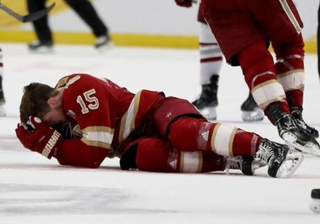 BUFFALO, NEW YORK - APRIL 11: Ian Mitchell #15 of the Denver Pioneers reacts after he is hit by Mitchell Chaffee of the Massachusetts Minutemen in the second period during the semifinals of the NCAA Men's Frozen Four at KeyBank Center on April 11, 2019 in Buffalo, New York. (Photo by Elsa/Getty Images)