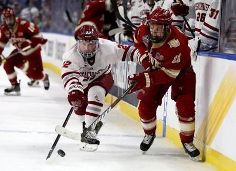 BUFFALO, NEW YORK - APRIL 11: Brett Boeing #22 of the Massachusetts Minutemen and Tyler Ward #11 of the Denver Pioneers fight for the puck during the semifinals of the NCAA Men's Frozen Four at KeyBank Center on April 11, 2019 in Buffalo, New York.The Massachusetts Minutemen defeated the Denver Pioneers 4-3 in overtime. (Photo by Elsa/Getty Images)