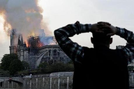 A man watches the landmark Notre Dame Cathedral burn, engulfed in flames, in central Paris on April 15, 2019. - A huge fire swept through the roof of the famed Notre Dame Cathedral in central Paris on April 15, 2019, sending flames and huge clouds of grey smoke billowing into the sky. The flames and smoke plumed from the spire and roof of the gothic cathedral, visited by millions of people a year. A spokesman for the cathedral told AFP that the wooden structure supporting the roof was being gutted by the blaze. (Photo by Geoffroy VAN DER HASSELT / AFP)GEOFFROY VAN DER HASSELT/AFP/Getty Images