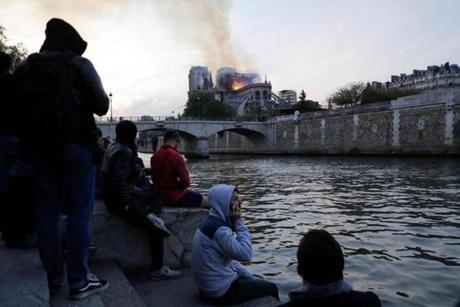 People look at smoke and flames rising during a fire at the landmark Notre Dame Cathedral in central Paris on April 15, 2019. - A fire broke out at the landmark Notre Dame Cathedral in central Paris, potentially involving renovation works being carried out at the site, the fire service said. (Photo by Thomas SAMSON / AFP)THOMAS SAMSON/AFP/Getty Images