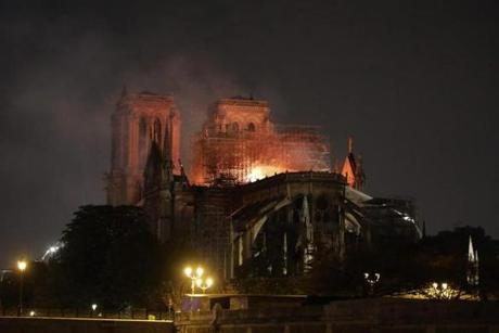 Flames are seen through the scaffolding as they engulf the roof of the Notre Dame Cathedral in Paris on April 15, 2019. - A colossal fire swept through the famed Notre Dame Cathedral in central Paris on April 15, 2019, causing a spire to collapse and raising fears over the future of the nearly millenium old building and its precious artworks. The fire, which began in the early evening, sent flames and huge clouds of grey smoke billowing into the Paris sky as stunned Parisians and tourists watched on in sheer horror. (Photo by ludovic MARIN / AFP)LUDOVIC MARIN/AFP/Getty Images